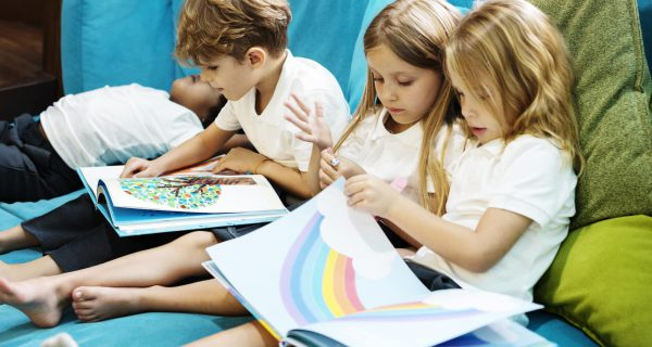 Group of Diverse Young Students Reading Children Story Book Toge
